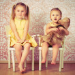 Two sisters sitting on a chair — Stock Photo