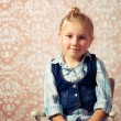 Little girl sitting on a chair - Foto Stock