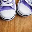 Colorful sneakers on wooden floor — Stockfoto
