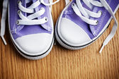 Colorful sneakers on wooden floor — Stock Photo