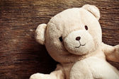 Teddy bear on old wooden background — Stock Photo