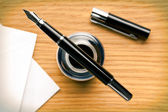 Fountain pen and inkwell on desk — Stock Photo