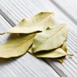 Bay leaves on white wooden table — Stock Photo