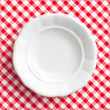 White old plate on checkered napkin — Stock Photo