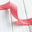 Checkered ribbon on white wooden table — Stock Photo