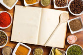 Cookbook and various spices and herbs. — Stock Photo