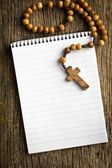 Rosary beads and blank notebook — Stock Photo