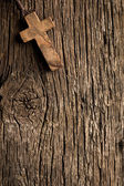 Antigue wooden cross on old wooden background — Stock Photo