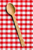 Wooden spoon on checkered tablecloth — Stock Photo