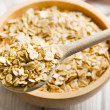 Oat flakes on a wooden spoon - Stock fotografie