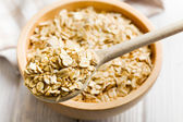 Oat flakes on a wooden spoon — Stock fotografie