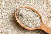 Wholemeal flour in wooden spoon — Stock Photo