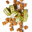 Brown sugar cubes and measuring tape — Stock Photo