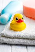 Yellow bath duck on white towel — Stock Photo