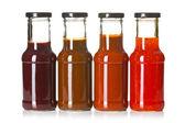 Varie salse di barbecue in bottiglie di vetro — Foto Stock