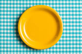 Empty plate on checkered tablecloth — 图库照片