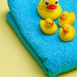Yellow bath duck on blue towel — Stock Photo