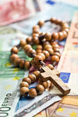 Rosary beads on euro currency — Stock Photo