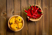 Red chili peppers and habanero on wooden table — Stok fotoğraf