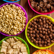 Various kids cereals in plastic bowls — Stock Photo