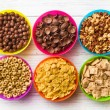 Various kids cereals in colorful bowls — Stock fotografie