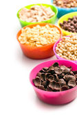 Various sweet cereals in colorful bowls — Stock Photo