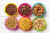 Various kids cereals in colorful bowls — Stok fotoğraf