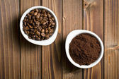 Coffee beans and ground coffee in bowls — Stock Photo