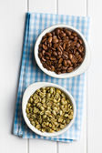 Roasted and unroasted coffee beans in ceramic bowls — Stock Photo
