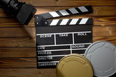 Clapper board with movie light and film reels on wooden table — Zdjęcie stockowe