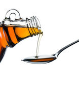 Maple syrup pouring on spoon — Stock Photo