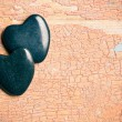 Black stone hearts on old cracked background — Stock Photo