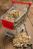 Wooden pellets in shopping cart — Stock Photo