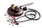 Judge's gavel with stethoscope and pills — Stock Photo