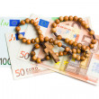 Stock Photo: Rosary with euro bills