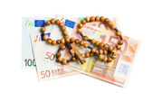 Rosary with euro bills — Stock Photo