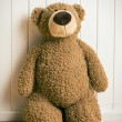 Teddy bear in front of  old wooden wall — Stock Photo #41492533
