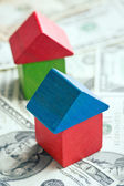 House made from wooden toy blocks on dollar background — Stock Photo