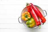 Colored peppers in colander — Stock Photo