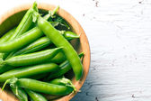 Green pea pods in wooden bowl — Stock Photo