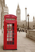 A traditional red phone booth in London with the Big Ben in a sepia background — Stock Photo
