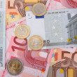 Euro banknotes with coins, financial background - Stock Photo