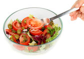 Fresh salad mix and fork with hand — Stockfoto