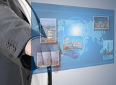 Businessman looking for tourism information using futuristic touch interface — Stock Photo