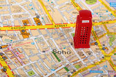 Small model of a red phone box  on top of a map of London — Stock Photo