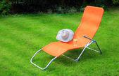 Orange lounge şezlong duran yeşil çimenlerin üzerinde — Stok fotoğraf