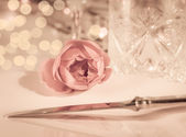 Elegant and romantic dinner setting with rose decoration and lights — Stock Photo