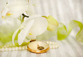 Orchid,pearls and golden swatch — Stock Photo