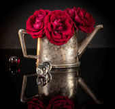 Red roses in old silver jug with glass balls — Stockfoto