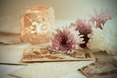 Golden pocket watch,old postcards and lacy candle with pearl necklace — Stockfoto